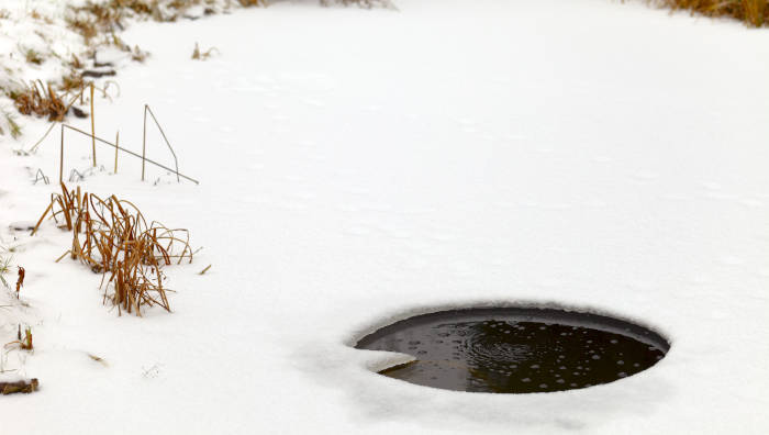 Gartenteich im Winter - ein Luftloch im Eis für die Fische