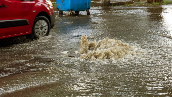 Überlaufender Kanal in einer Straße, Regenwasser oder Mischwasserkanalisation